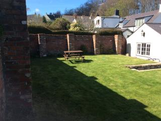 Walled garden with apple trees and well tendered borders and steps leading to the Patio.