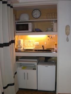 cozinha compacta para aquecer refeições rápidas. Micro-ondas, cafeteira e torradeira.