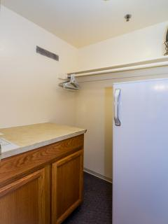 Refrigerator in the walk-in closet behind the kitchen.