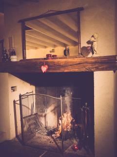 La cheminée avec son panier de bois.