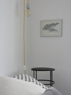 Bedroom detail, with iron bedside table, lamp and original ink drawing.