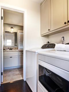 Powder and laundry room, fully stocked with fluffy towels, iron and iron board.