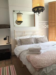 second bedroom with comfy double bed, plantation shutters open wardrobe and storage shelving