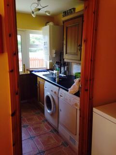 Utility room beside kitchen with washing machine / dryer.