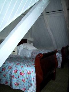 attic bedroom with two single beds, adjacent sitting area, toilet and sink