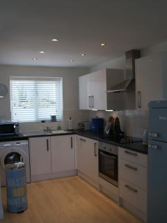 Fully fitted kitchen with modern appliances, including integrated dishwasher