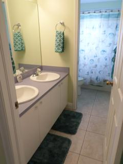 Main bathroom with dual sinks and bathtub/shower