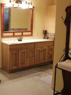 A spacious bathroom with a tall shower.