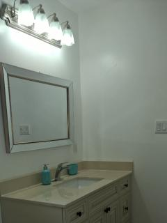 The bathroom has a large vanity mirror and cabinet.