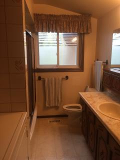 Full bathroom with regular size tub, washer and dryer