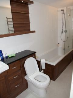 En-suite bathroom - bath and shower over, walnut vanity unit