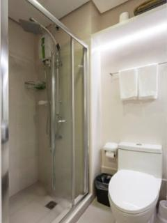 Toilet and baths has a granite top with wash basin, hot & cold showers, towels and toilet paper.