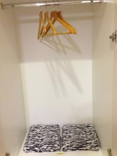 Closets supplied with blankets and wooden hangers.