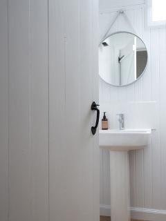 The bathroom is bright and airy with a shower