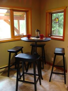 Kitchen features a cafe table with stools for a bite of breakfast or a quick snack