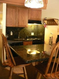 Your fully equipped kitchen with granite counter top and seating for four people.