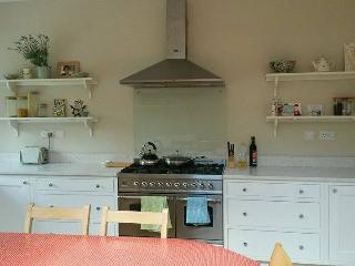 Large sunny kitchen with range cooker and extending table.