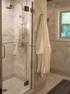 The shower features multi-head shower with Italian Carrera marble and a glass door.