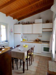 La luminosissima cucina, con tetto in legno e accesso al balcone con tettoia.