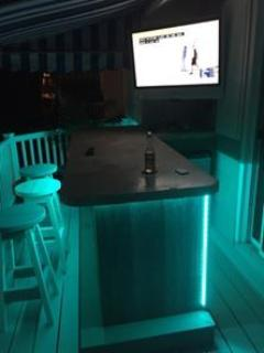 The outside bar at night with a 42 inch flat screen Seating for 6