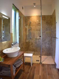 Luxury bathroom with walk in shower, modern washbasin on teak stand. Marble tiles.Underfloor heating