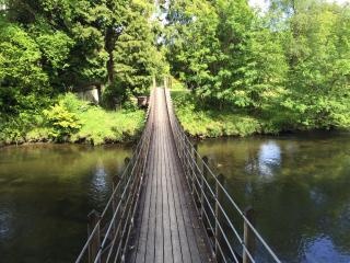 Swing bridge over river leading to caer beris manor hotel