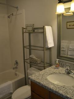 The  bathroom  while compact is all new and has a curved shower rod for extra space in the tub