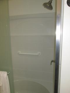 2-seat shower with grab bar.