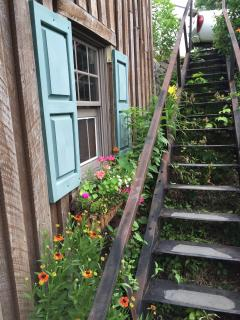 Vintage iron outside stairs lead to lower level entry. Gardens and herbs on each side.