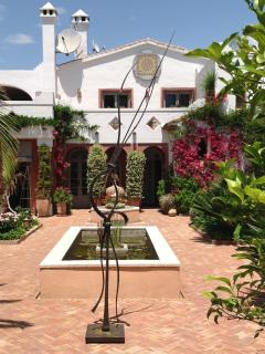 The garden in May with bougainvillea in full bloom and metal art by Sebastian Fisher.
