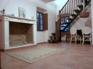 Il camino decorativo in salotto e la scala che porta al piano superiore