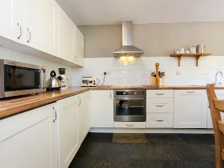 The well equipped kitchen boasts a large dining table and plenty of work space