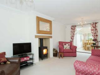 Main sitting room with log burner, comfortable seating and door to conservatory