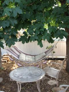 Shaded back yard relax area, cement patio located beside the maple trees