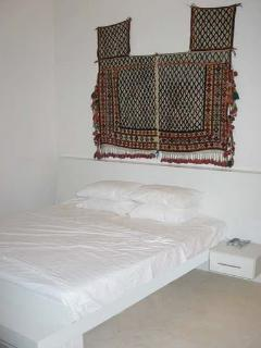 main bedroom suite and antique textile