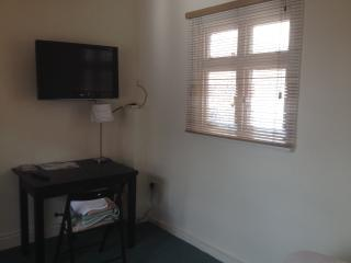 Opposite view of studio room with large TV, table & dining chairs.