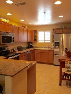 Kitchen with stainless steel appliances and granite counters. Butcher block chopping table.