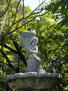 A statue peeps out of the borders in the grounds of The Trinities