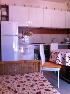 cucina con mermo di carrara, lavastoviglie, divano letto e tavolo