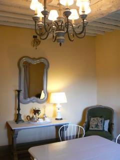The mirror over the marble topped side table reflects the views of Tuscany and the chandelier