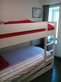 La chambre enfants et sa fenêtre. 2 lits superposés face a face pour 4 couchages