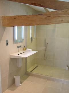 The mix of old beams and modern fittings in the shower room
