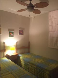 dormitorio con dos camas y ventilador de techo