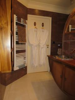 The bathroom with towels,  bathrobes, slippers and organic cosmetics