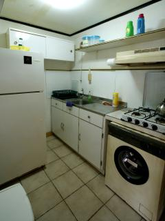 Kitchen has full-size fridge, gas cooktop and washing machine.