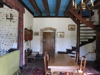 le salon avec ses poutres apparentes et l'escalier à vis pour accéder au 1er étage