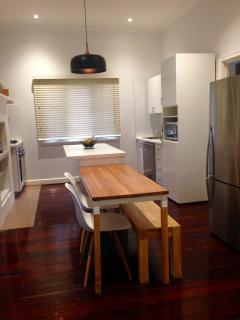 Modern kitchen with microwave, dishwasher, oven, large fridge and plenty of cupboard space.