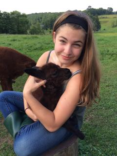 Ariana with a newborn alpaca known as a cria. The Cria's name is Zeus  They are so cute and friendly