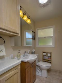 Bathroom with full size tub and shower is centrally located between kitchen and bedrooms.