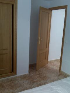 Picture of part of bedroom one, including built in wardrobe and door